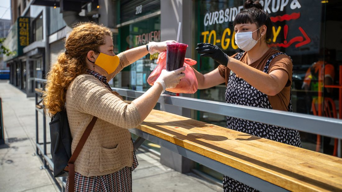 Restaurant owner serves customer at outdoor pick-up during pandemic