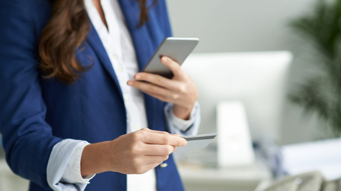 woman holding credit card and making phone call