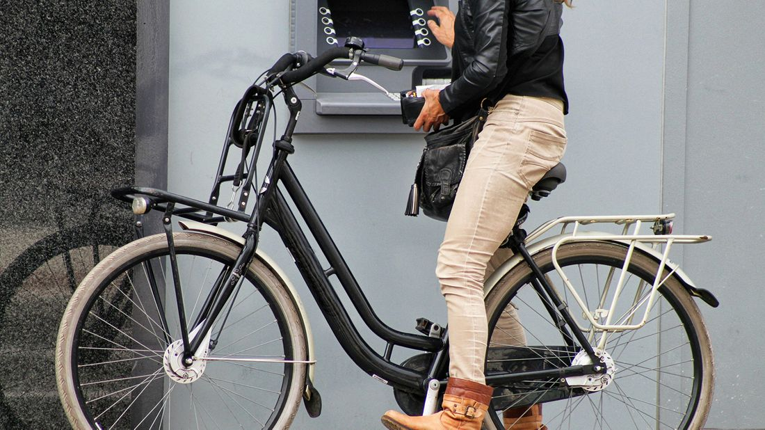 woman on bike using atm