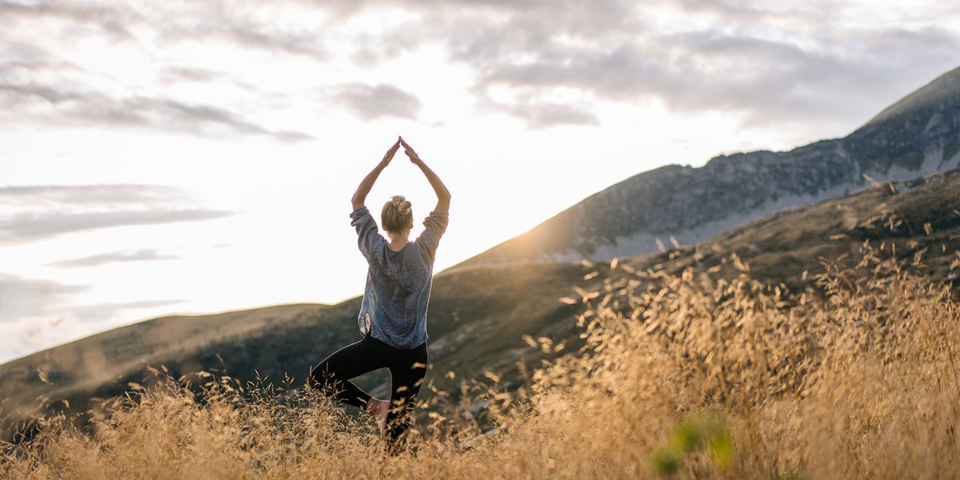 Woman doing yoga in the mountains while thinking about financial wellness.