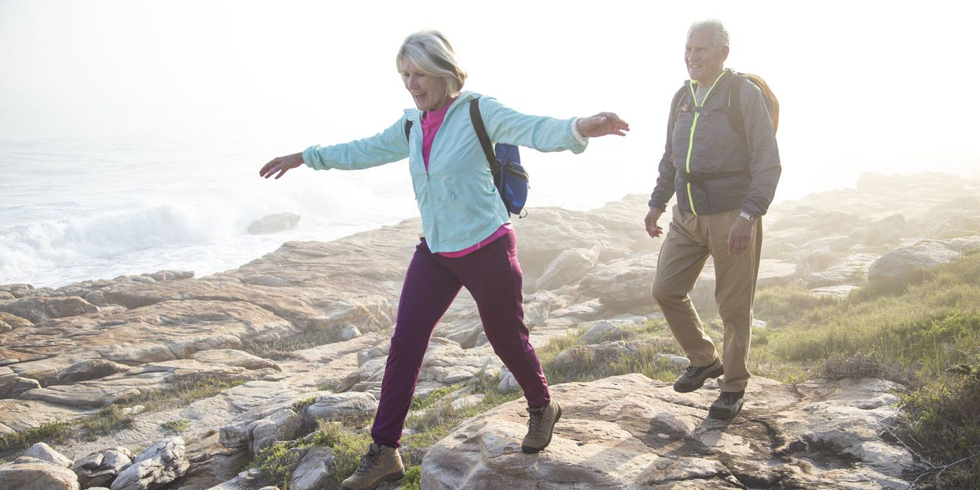Active retired couple enjoying a hike over a rocky shoreline