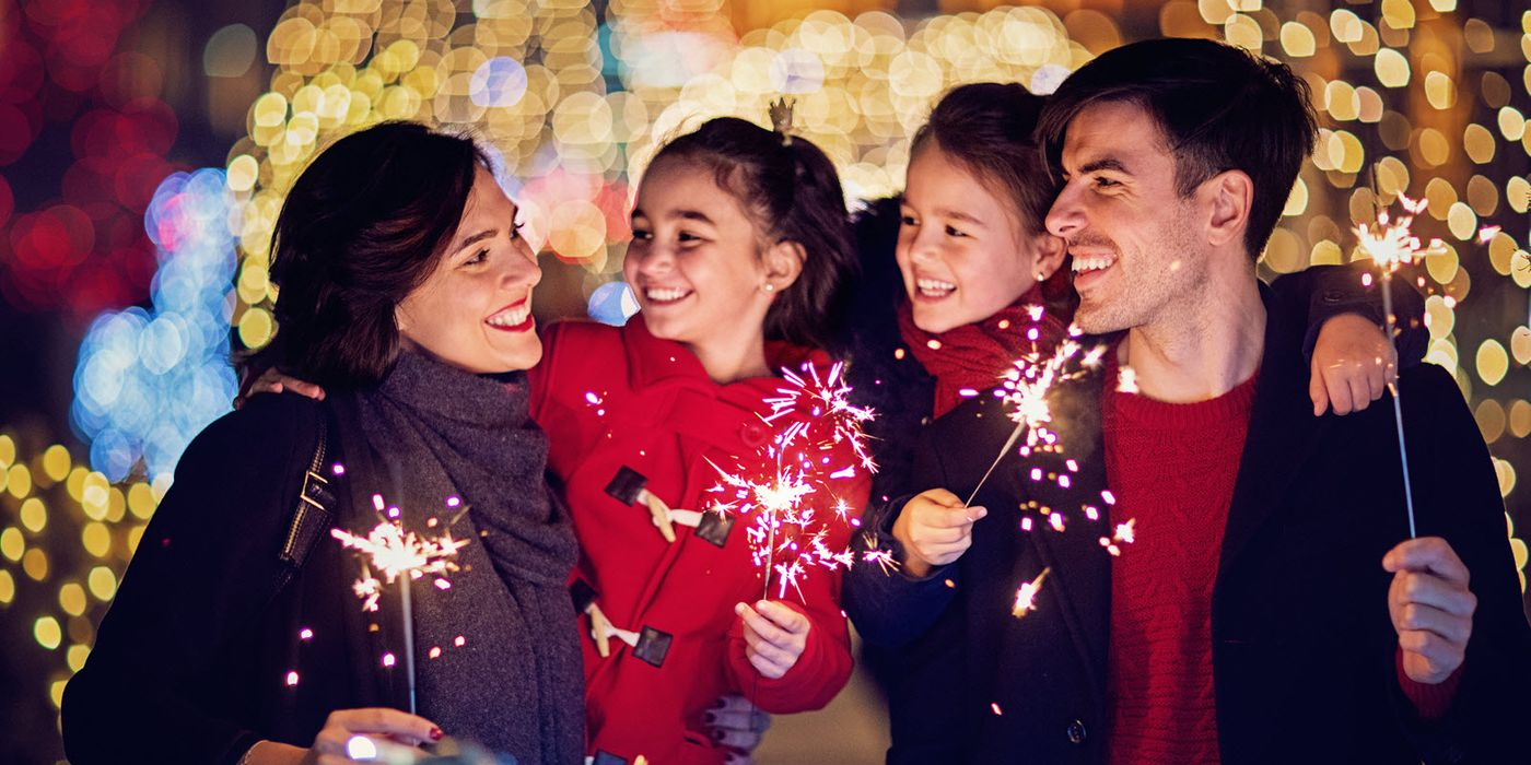 Family holding sparklers as they consider their financial goals for 2018.