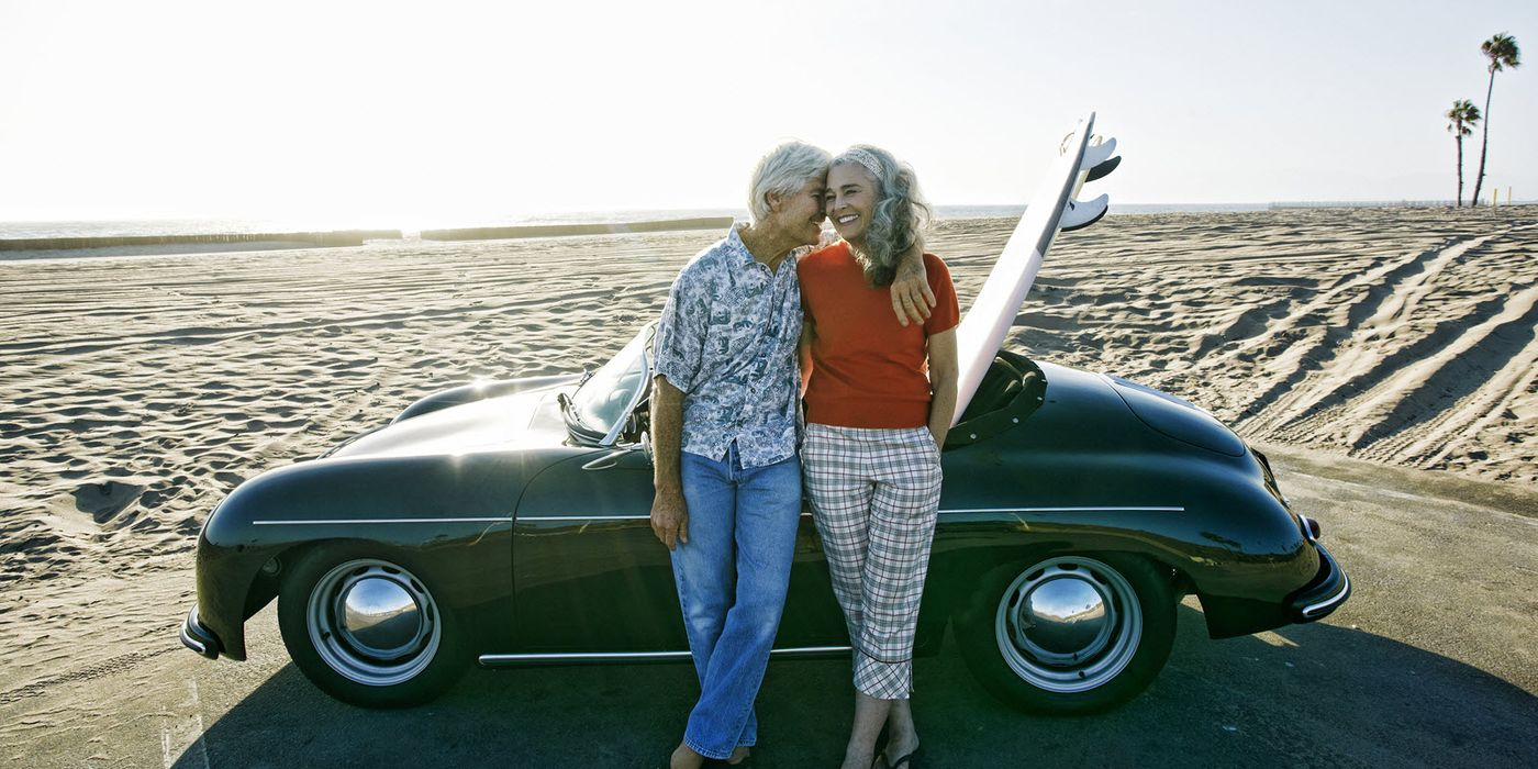 Retired couple posing in front of a car at the beach.