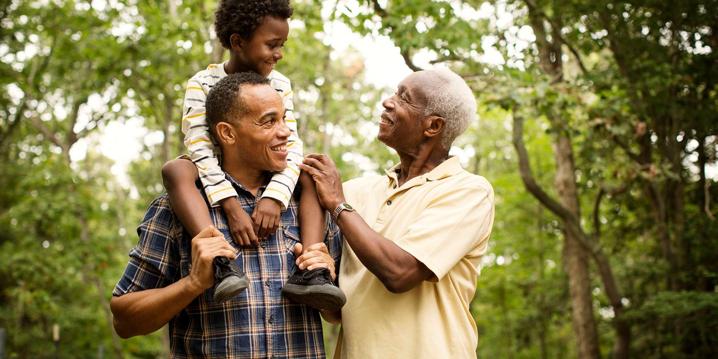 grandfather, son and grandson walking in park