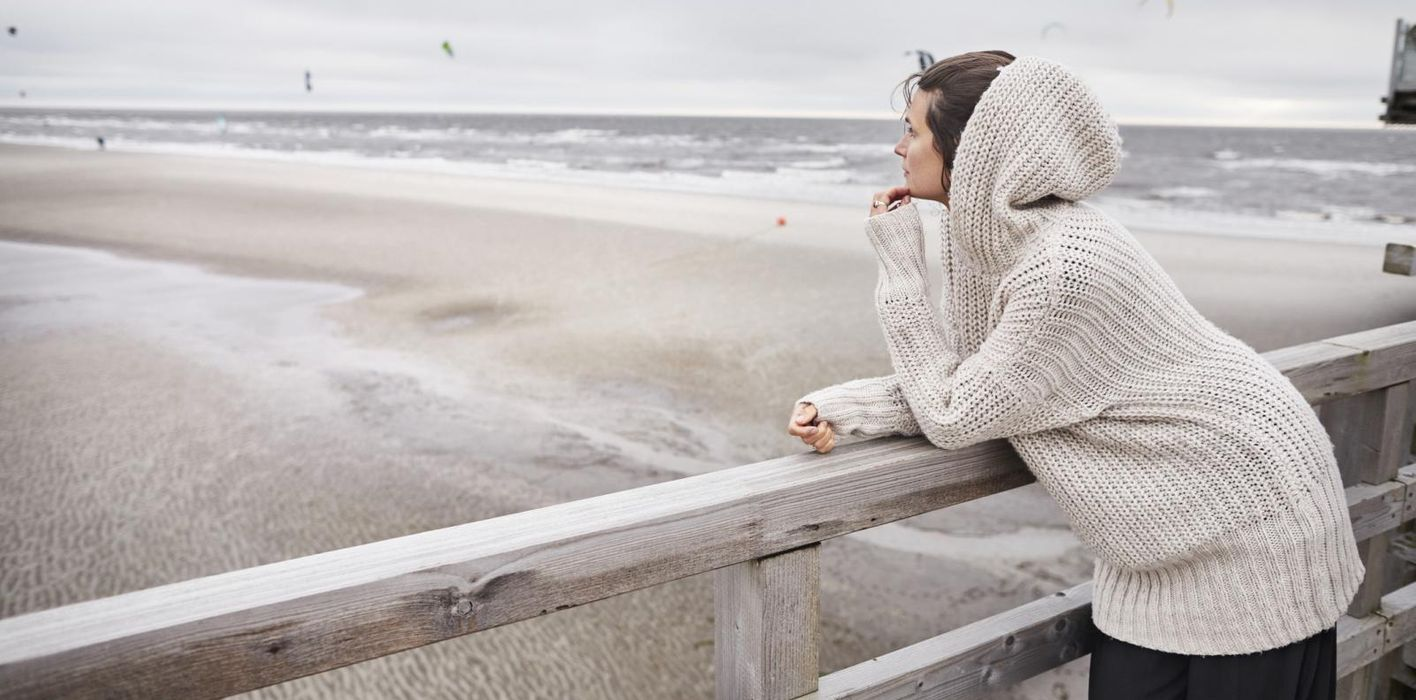 Resilient woman standing on a footbridge near the ocean