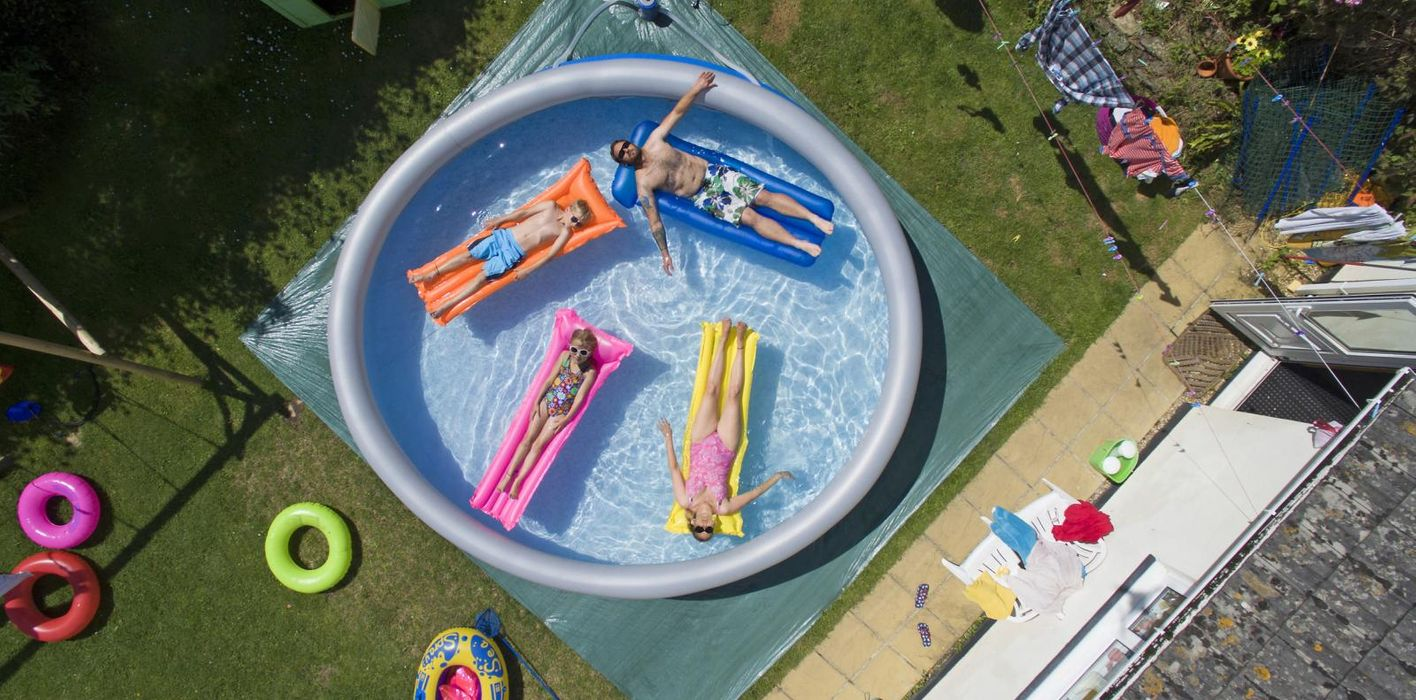 family in large padding pool in upgraded backyard