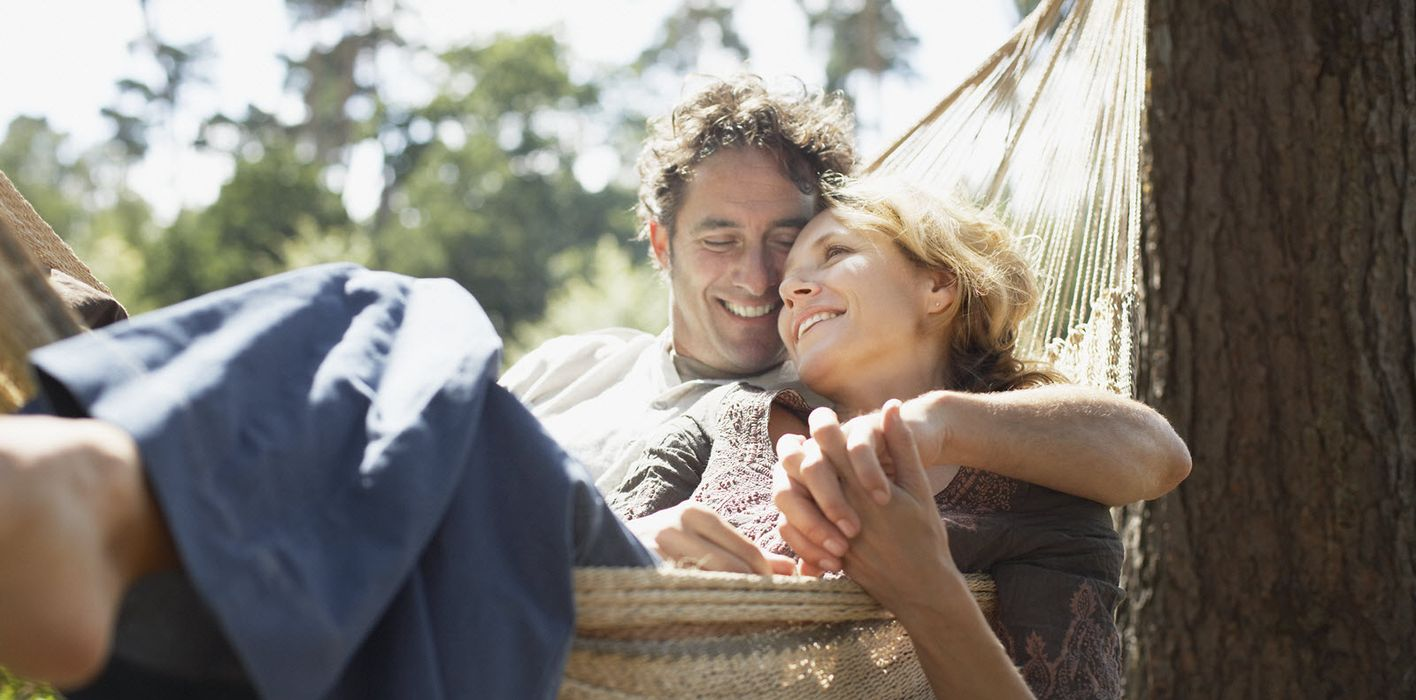 Couple snuggling in a hammock wondering if they need life insurance after 65