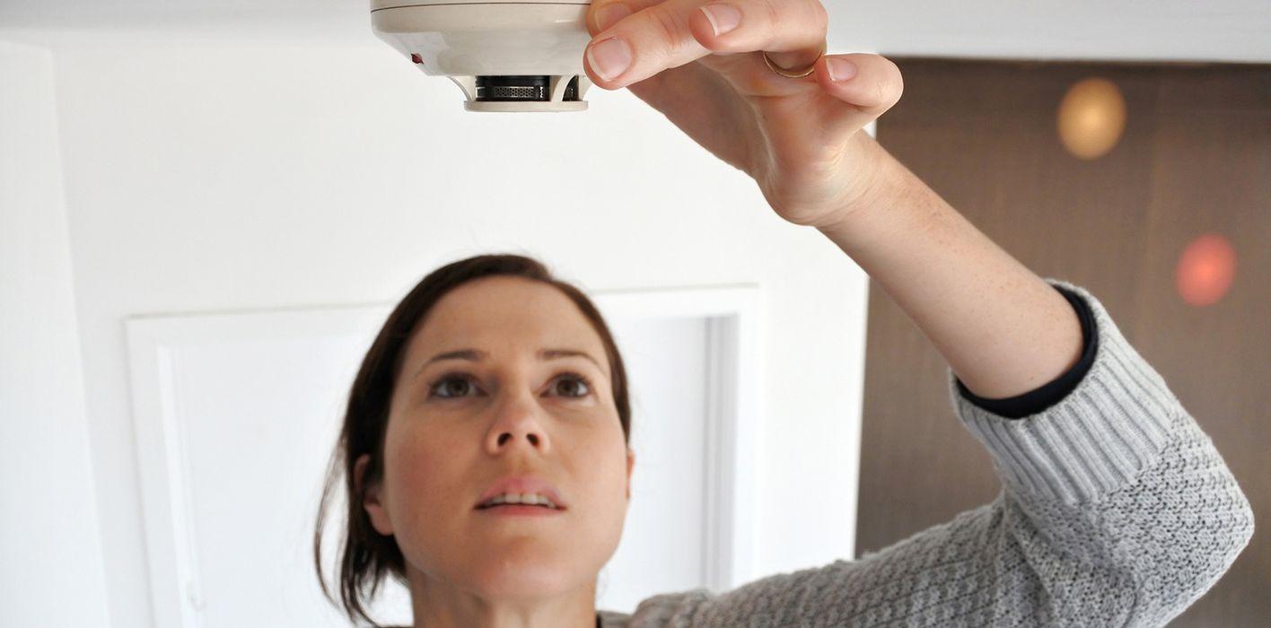 woman checking smoke detector