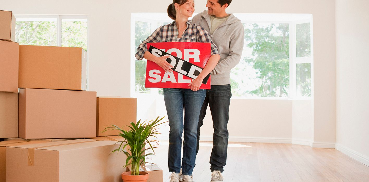 Couple holding sold sign after winning a bidding war.