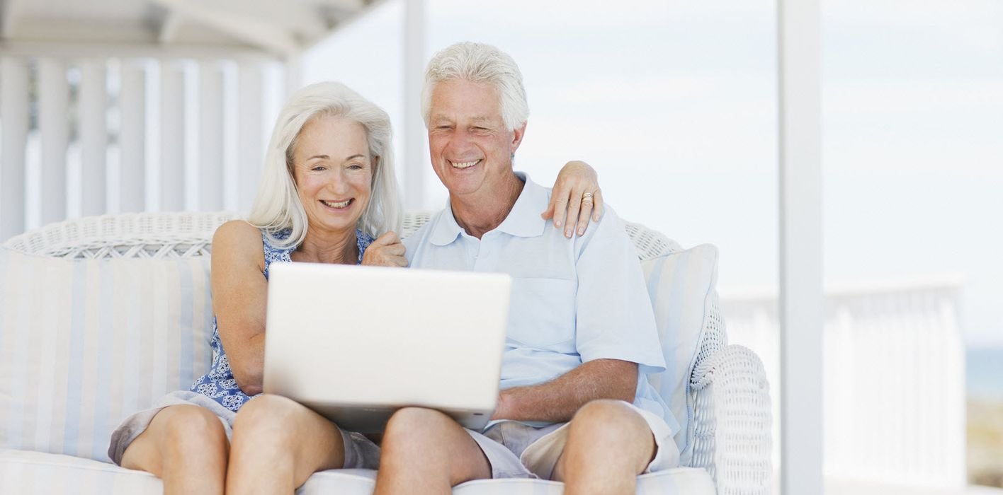 Couple sitting on porch reading Northwestern Mutual Market Commentary