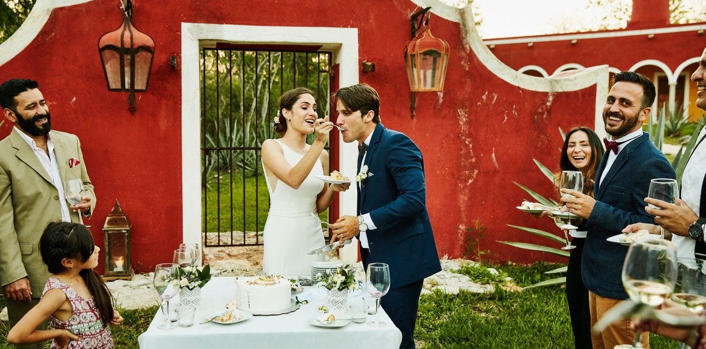 newlyweds cutting cake at reception ceremony