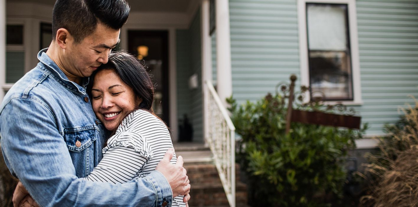Young couple hugging in front of new home