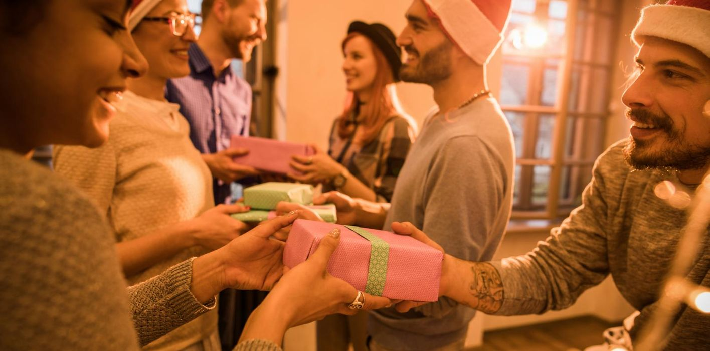 Colleagues exchanging gifts during holiday office party