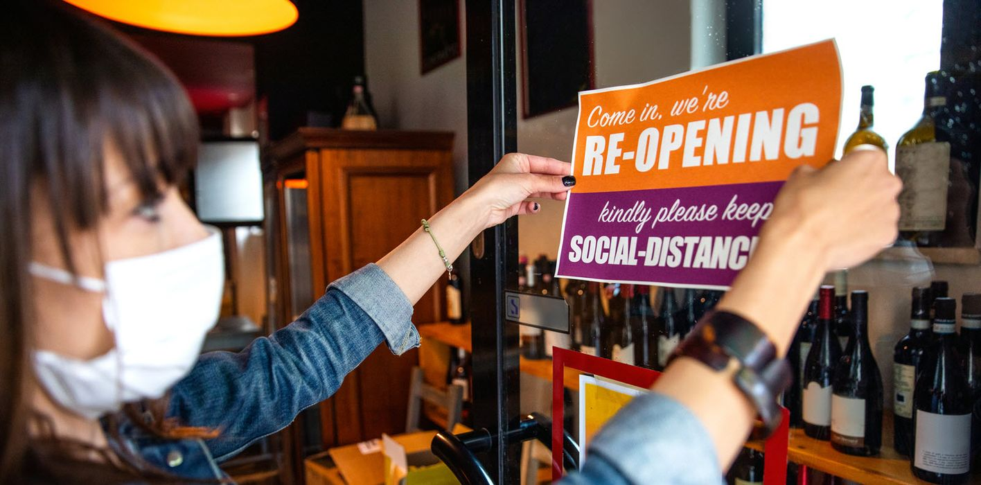 A shop owner displays an open sign with social distancing recommendations