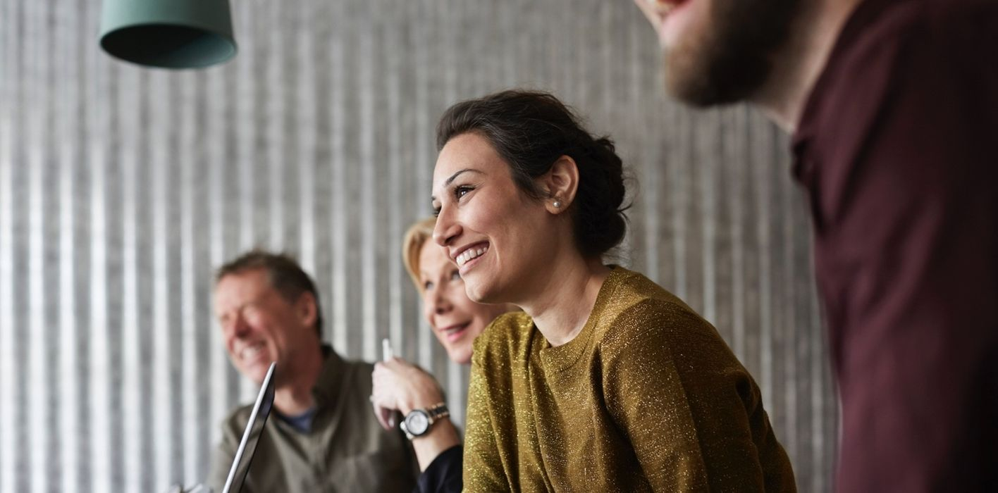 Woman in business meeting smiling.