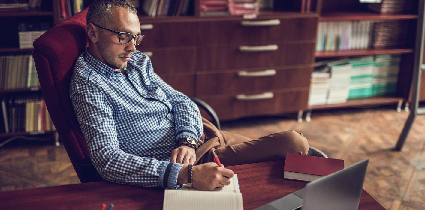 Man taking notes at his desk.