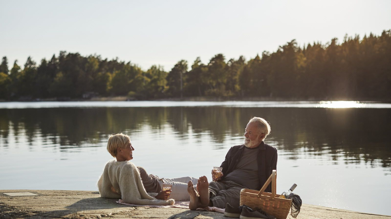 Couple having a picnic by a lake and discussing how does an annuity work.