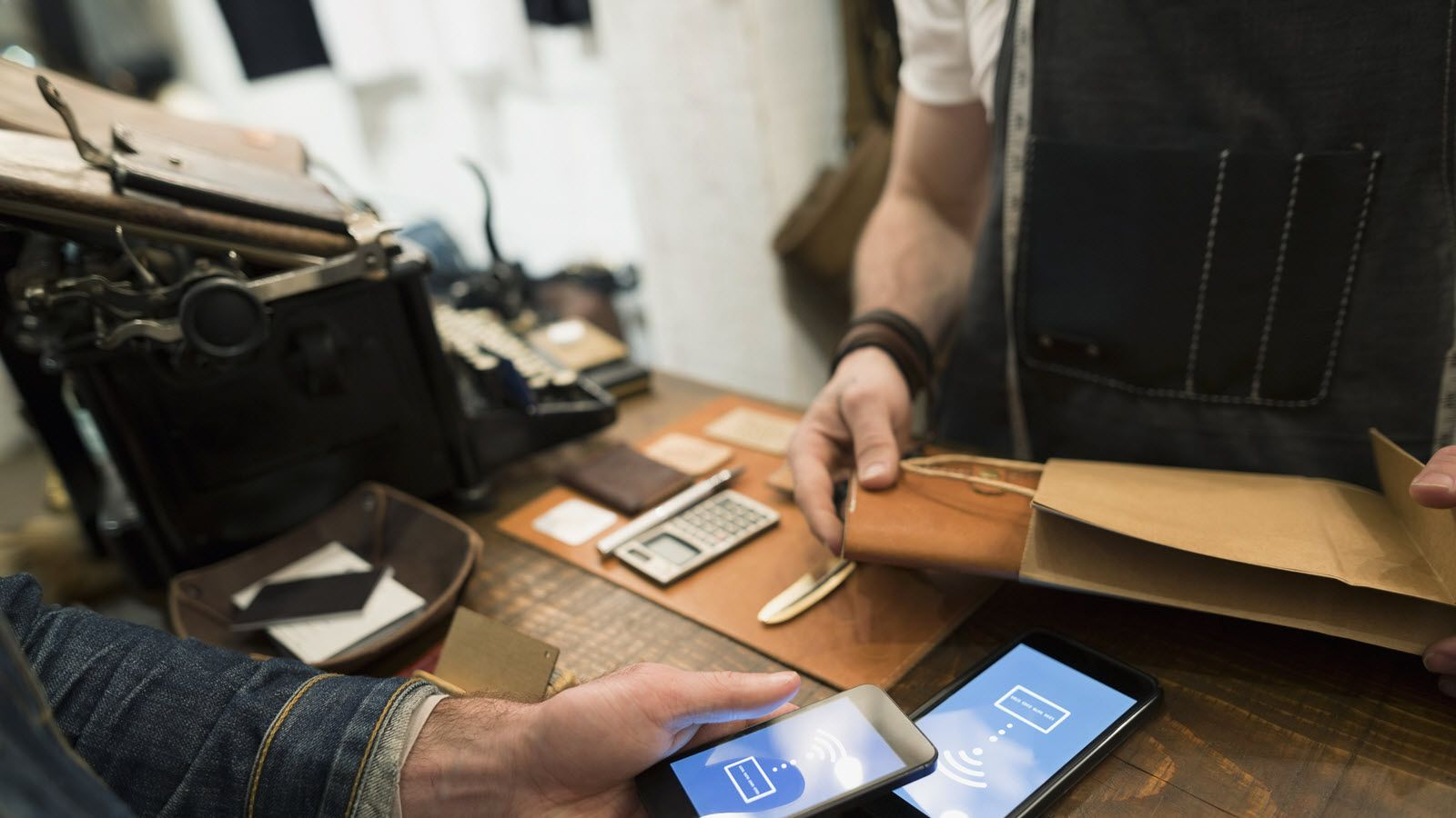 A customer uses smartphone to make a cashless purchase at small business