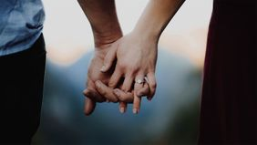 Engaged couple holding hands wondering how much an engagement ring costs