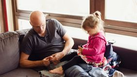 Rasing children later in life dad and daughter on the sofa