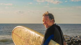 Older man with a surfboard after learning the estate planning process
