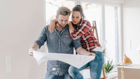 Couple looking at floor plan wondering if they should DIY home projects