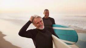 Older men surfing after managing debt in retirement