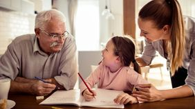 An elderly parent helps graddaughter with her homework