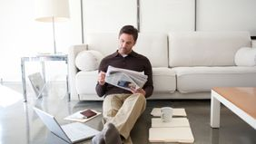 Man at home reading news about how coronavirus is impacting your finances.