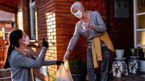 Volunteer bringing groceries to a senior woman at home during the coronavirus