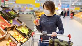 Woman grocery shopping whose budget is impacted by the coronavirus.