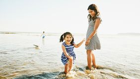laughing young girl playing with mother at the beach