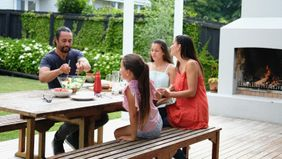 family enjoying summer lunch on outdoor patio
