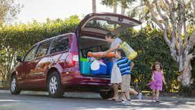 Family packing their van after paying down their car loan