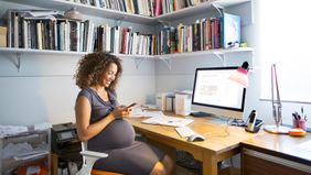 pregnant woman sitting at desk at home