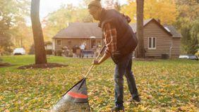man raking leaves in backyard