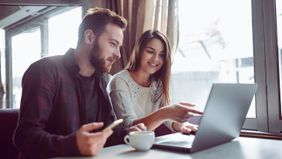 couple drinking coffee while working on their financial resolutions