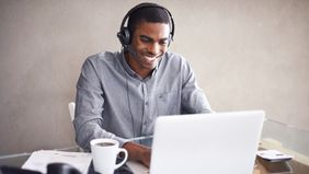 young man wearing a headset while working on his laptop