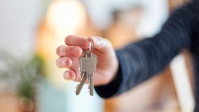 Man holding new house keys after getting mortgage while unemployed
