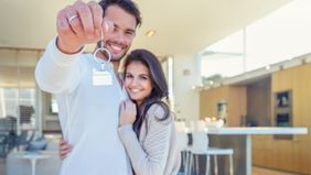 couple holding keys to their new home because they ignored mortgage misconceptions.