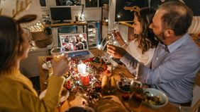 Family sharing holiday experience with friends on video call