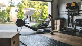 woman working out on rowing machine in garage