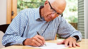 Older student loan co-signer filling out paperwork