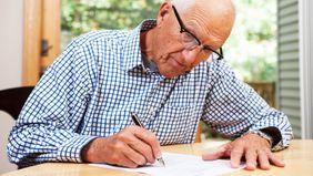 Older student loan co-signer filling out paperwork