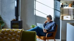 Man sitting in a chair in his loft researching can I avoid paying taxes on my 401(k) withdrawal.