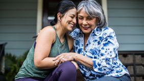 Woman and elderly mom hugging.