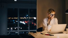 woman using laptop while managing her stress