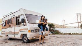 man giving woman a piggyback in front of an RV