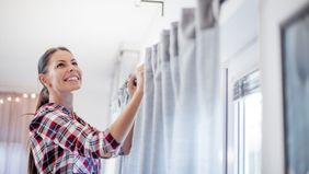 woman hanging curtains