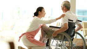 Home health aide helping a senior man with the activities of daily living.